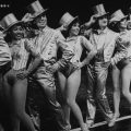 1940ish Broadway dancers lined up on stage tipping top hats