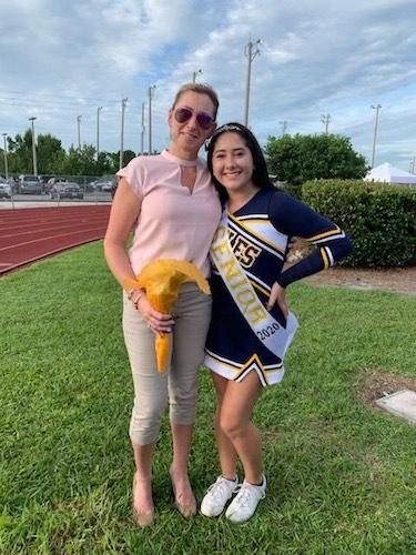 A mom standing next to her jigh school seniots cheerleader