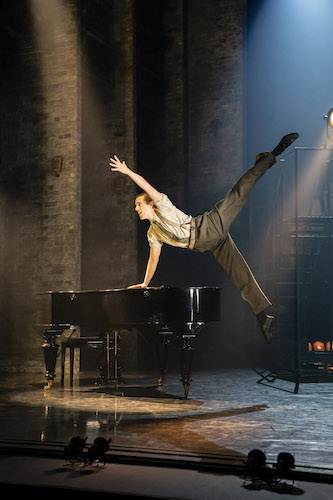 Red Shoes male dancer leaping while leaning on piano