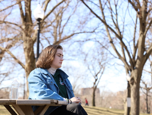 Teen sitting at picnic table in park