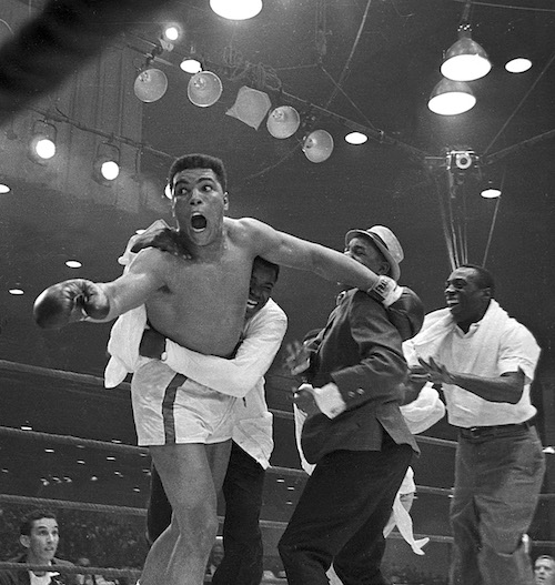 Cassius Clay's handlers hold him back as he reacts after he is announced the new heavyweight champion of the worl