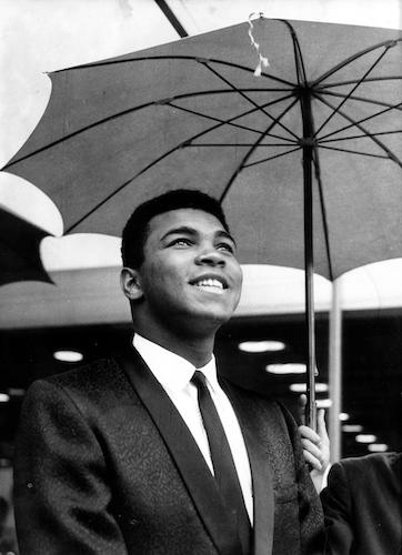 Muhammad Ali smiling as someone holds umbrella for him