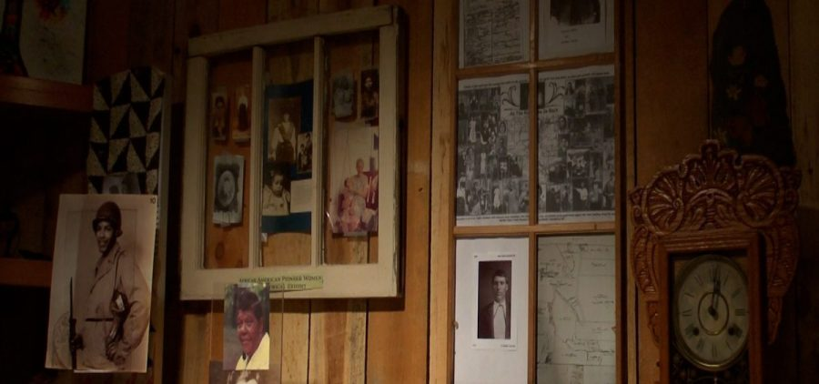 Framed photos of Butcher Family sit against wooden wall.