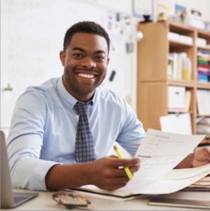 teacher grading papers at desk