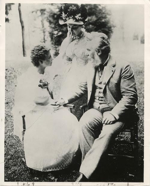 Black and white image of Helen Keller sitting with Anne Sullivan and Alexander Graham Bell