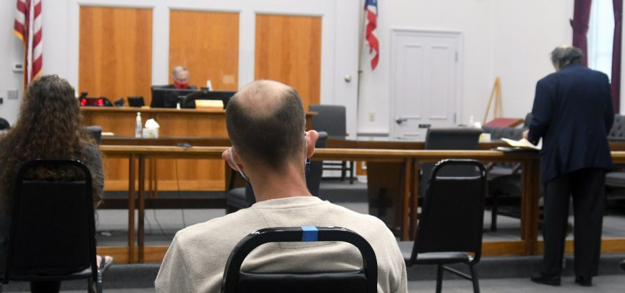 A court room in Athens County with the judge hearing from an attorney while two people look on.