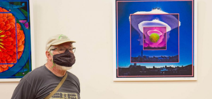Artist John McVicker poses with one of his digital collages included in an exhibition of his work at Stuart's Opera House