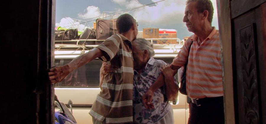 elderly woman hugging man at doorway entrance