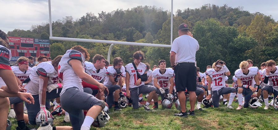 St. Clairsville players kneeling and surrounding their coach while he gives them a pep talk