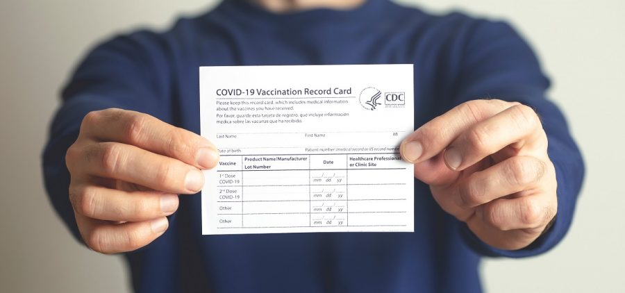 Vaccination form during the coronavirus epidemic in the hands of a vaccinated man.
