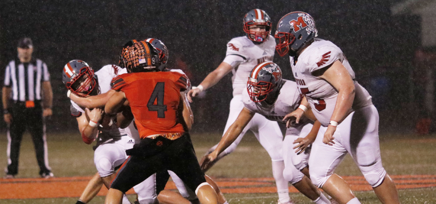 Minford player wrapped around the shoulders by a Waverly defender