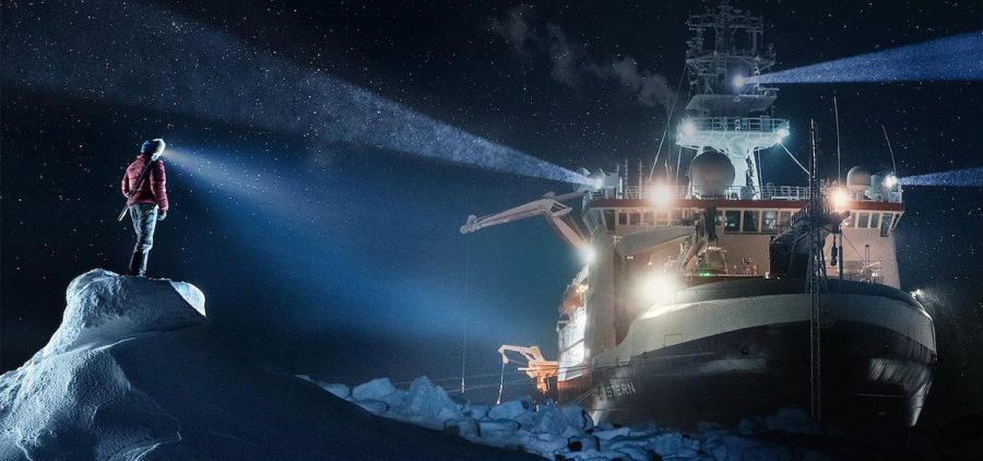 explorers witrh headlamp on ice shining out towards ship