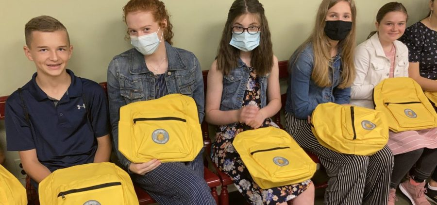 Students hold their backpacks supporting school choice legislation.