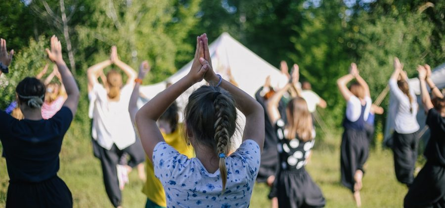 Group of children doing morning exercises hands up yoga sport outdoors in nature in summer camp